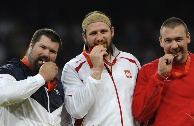图文-[奥运]田径男子铅球决赛 前三名品尝奖牌滋味