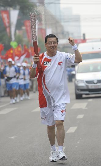 图文-奥运圣火在北京首日传递 火炬手龙永图