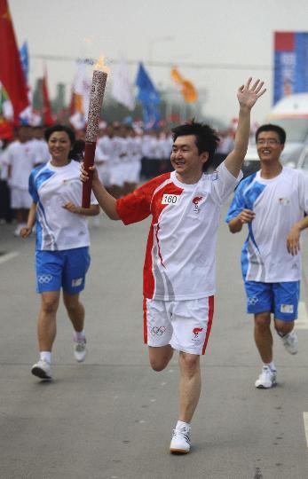 图文-奥运圣火在四川成都传递 火炬手王小川