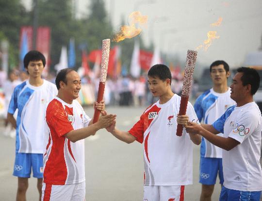 图文-奥运圣火在四川成都传递 陈勇与周仕强交接