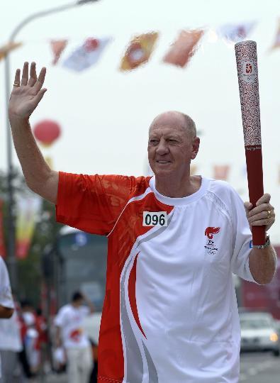 图文-奥运圣火最后一日传递 内维尔挥手示意