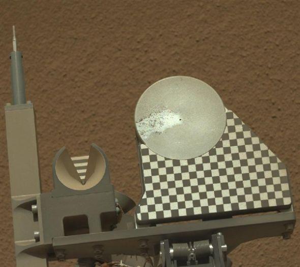 """10月16日,也就是""""好奇""""号在火星上度过的第70个火星日,""""好奇""""号的机械臂首次将火星土壤样本放上观测盘。照片由""""好奇""""号的桅杆相机拍摄,展示了观测盘上的土壤样本。观测盘直径3英寸(约合7.8厘米),样本来自于一个名为""""岩巢""""的区域。10月15日是""""好奇""""号在火星上度过的第69个火星日"""