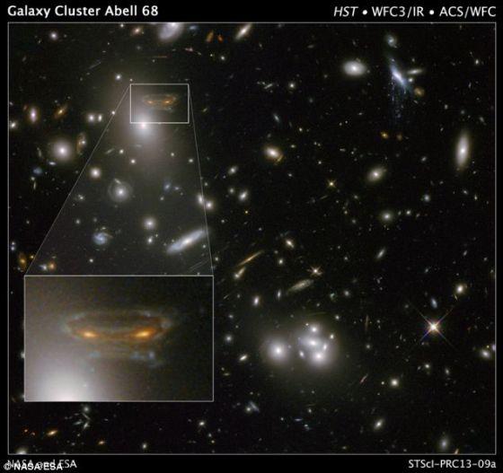 """在哈勃望远镜拍摄的这幅照片中,背景螺旋星系被扭曲变形,好似一个太空入侵者。前景巨型星系团被称之为""""Abell 68"""",距地球20亿光年。亮度增加同时扭曲变形的镜像来自于后面更为遥远的星系"""