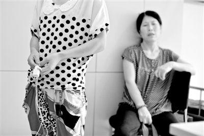 昨日,武建同的妹妹手拿事发时的充电器站在海淀医院ICU病房外,等候哥哥醒来。新京报记者 周岗峰 摄