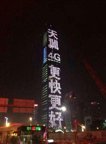 """在深圳高达441.8米的京基100大楼,其2.6万平米外墙出现""""天翼4G更快更好""""大字"""