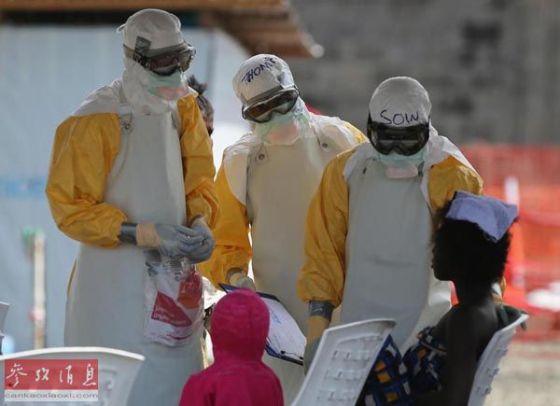 西非利比里亚疫区,几名医护人员正在为一名埃博拉感染者查体。(美联社)