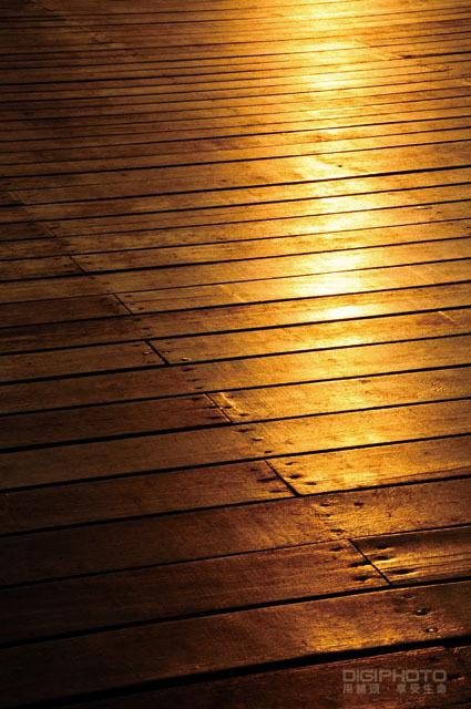 落日的橘色与深褐色的木栈道传达出简单温暖的感受