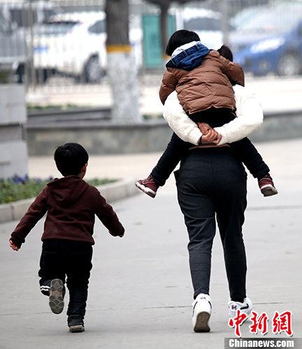 图为郑州民众带着小孩出门玩耍。 中新社记者 王中举 摄