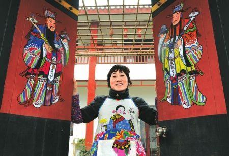 绵竹孝德年画村一位村民站在自己的新院门内。