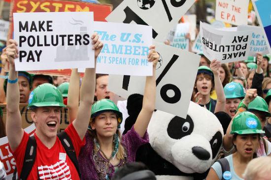 圖為抗議者在拉菲特廣場手舉標語要求大型油企為環境污染買單。