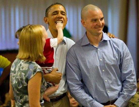 圖為庫柏把小手放進奧巴馬嘴裏,右為孩子父親格雷格,他完全不知身後發生了什麽隻顧合影,而孩子母親梅裏迪斯隻是注視著這好玩的一幕
