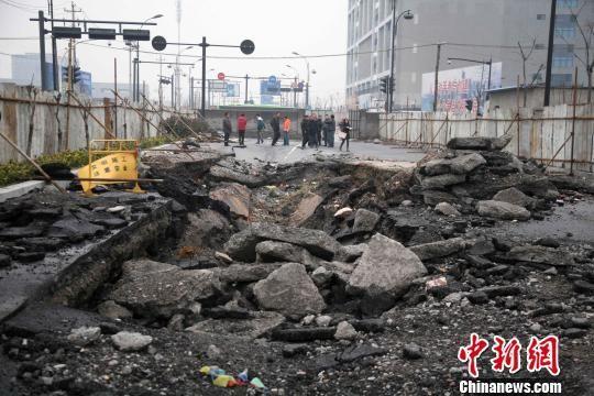 27日下午,杭州地铁一号线终点站附近的胜稼路与九沙大道交叉口北侧一段路面,出现了大面积塌陷路面,开裂塌陷大坑约3米多深。 李晨韵 摄