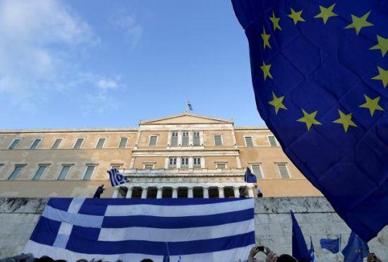 6月22日,集会者在希腊议会外挥舞希腊国旗与欧盟标识旗,呼吁希腊政府与国际债权人达成协议。 REUTERS/YANNIS BEHRAKIS