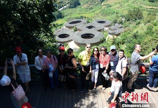 图为海外华文媒体代表与土楼群合影。 张金川 摄