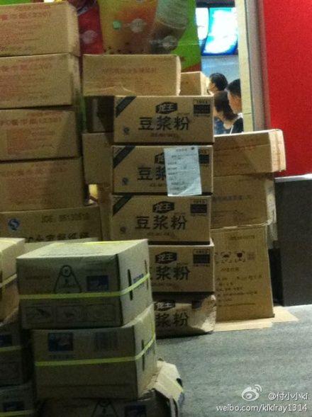 图为网友曝出的肯德基门店外堆放着几箱豆浆粉原料。(来源:网友微博上传)