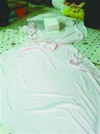 下图:车间的地上铺着一块布,洗干净的床单将在这里被打包。 本报记者 摄