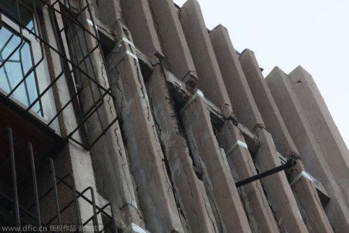 2014年10月8日,山东济南,历山东路2号一居民楼出现楼体柱子多处开裂,用透明胶带捆绑固定的情况。一些居民反映,外出家门十分担忧,有时抱头出行。