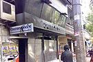 一男子站在被破坏的店铺前