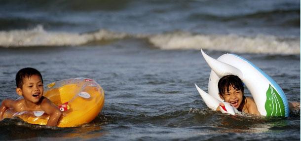 海南琼海儿童在博鳌海滨戏水纳凉