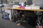 工作人员在桌下避难