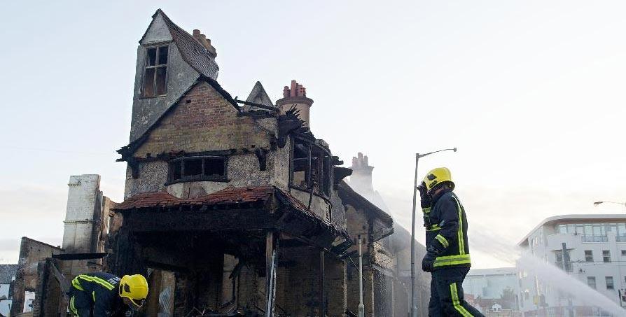 消防员向被烧毁的家具店喷水