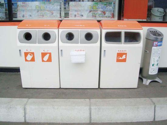 """日本一家超市前的垃圾回收装置:可投放标示从左至右为""""易拉罐、玻璃瓶、塑料瓶、易燃垃圾"""",最右边的是顶部设有烟灰缸(以备顾客吸烟)的普通垃圾桶。"""