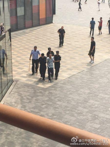 图为嫌疑人被警方带走。