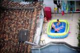 图文:小女孩在自家天台上的迷你游泳池里戏水