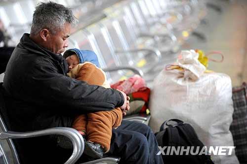 组图:旅客在除夕夜的火车站等待回家