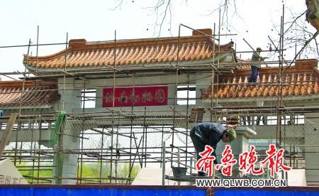 7日,济南动物园正门牌坊处,工人们为这个与该园同龄的老牌坊美容.