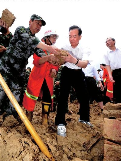 温家宝在广西灾区挽裤脚泥地里清理砖块