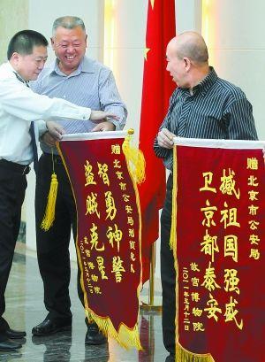 """昨天,故宫博物院负责人来到北京市公安局,向快速侦破故宫失窃案的市局有关部门赠送锦旗。锦旗中的""""撼""""字应为""""捍""""。本报记者 贾同军摄"""