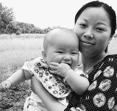 5月15日,吴菊萍抱着儿子在浙江嘉兴市秀洲区王江泾镇的老家留影。新华社发