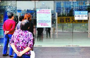 昨日,市民在沃尔玛门口阅读告示。重庆晨报见习记者 王海 摄