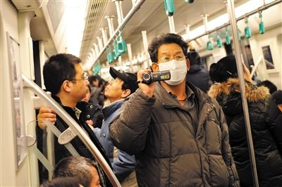 昨日下午,8号线列车上,一位大爷用摄像机记录着新车的一切。