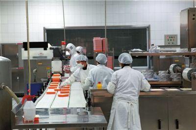 昨天,北京铁路局动车段配餐中心内,米饭装盒正在进行。本报记者王海欣摄