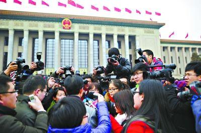 参加会议的全国政协委员在人民大会堂外被记者围上了。特派记者 周超 摄