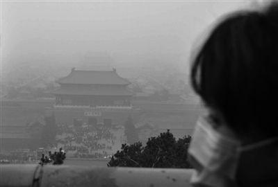 3月17日 北京大雾天气,市民戴着口罩站在景山公园最高点观看雾海里白茫茫的故宫。实习生 刘梦 摄