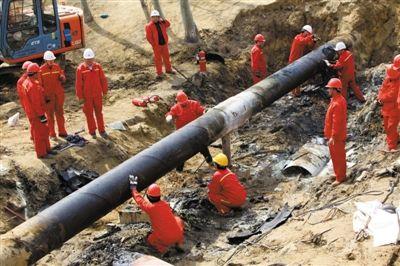 挖掘机将地面挖开后,工人正在抢修河道中的输油管道。