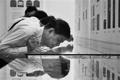 昨日,首都博物馆,一位观众摘下眼镜凑近展柜玻璃仔细看印章。 实习生 刘梦 摄