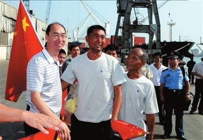 昨天,在达累斯萨拉姆市港口,中国大陆船员、大副李东利(左二)与国内赶来的同事相拥。新华社发