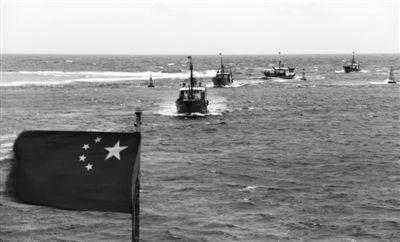 海南赴南沙捕捞船队列队驶入美济礁��湖。由于南海热带低压生成,7月20日,海南赴南沙捕捞船队转场至美济礁,进入美济礁礁盘内先行避风休整,待天气好转后择机作业。王晓彬 摄