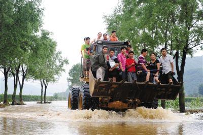 8月5日,辽宁省岫岩县大隈子村村民乘铲车撤离受灾地区。前日,因台风影响大隈子村遭受洪涝灾害。 新华社记者 潘昱龙 摄