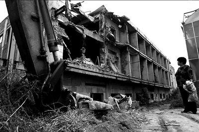 21日中午,一名路过的冯村村民,望着被拆迁的房屋出神。本报记者 谭青 摄
