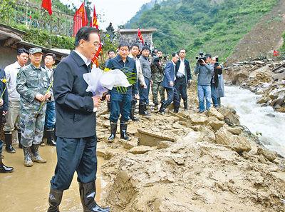 10月5日,温家宝缓步走到淹没田头小学的滑坡体前,向遇难的孩子和村民献上一束菊花。
