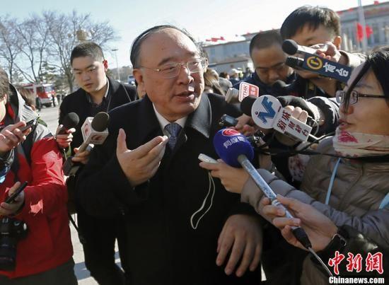 3月4日上午,十二届全国人大一次会议预备会议在北京人民大会堂举行。全国人大代表、重庆市市长黄奇帆进入会场前回答记者提问,他表示欢迎记者到重庆来看看。中新社发 张浩 摄