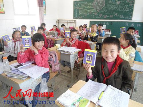 学生刚刚领到《新华字典》后开心地笑了
