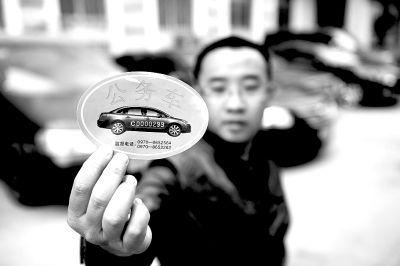 青海省某单位一名驾驶员在展示领取的公务用车标识。记者 张宏祥 摄