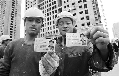 去年10月29日,山东青岛市,工人们正在展示刚领到的居住证。图/CFP