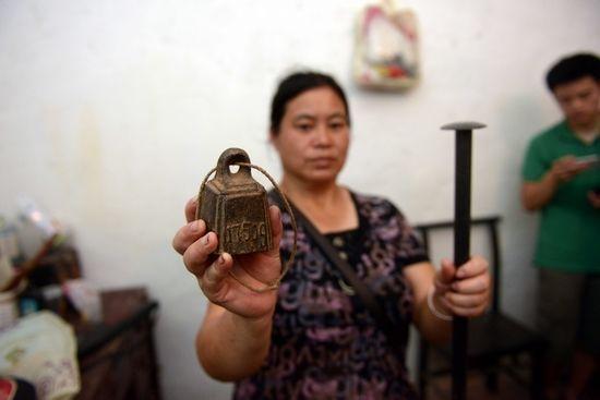 邓正加的家属向记者展示秤砣和铁棍。